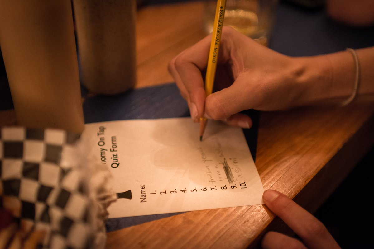 An audience member diligently fills out answers for our astonomy-themed pub trivia.