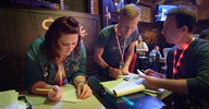 Rebecca Larson, Cameron Hummels, and Andreas Faisst work to grade the pub trivia forms and award prizes.