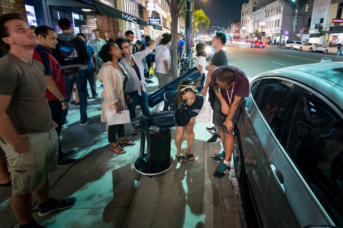 Michael Zhang helps someone to view Jupiter for the first time on the sidewalk in Old Town Pasadena.