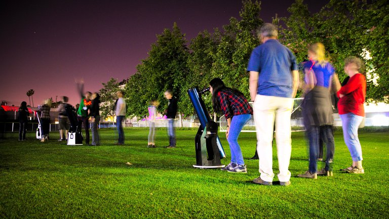 A stargazing session on the athletic fields following the conclusion of the public lecture.
