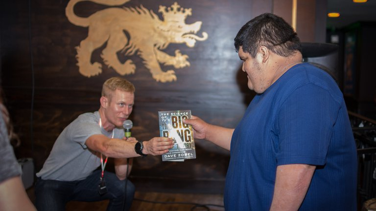 Cameron Hummels presents a prize to one of the winners of the pub trivia.