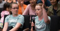 Two enthusiastic young audience members ask a question at a Stargazing Lecture.