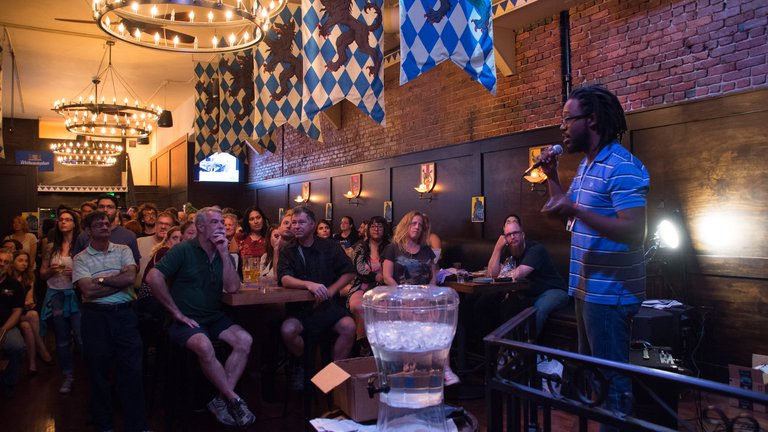 Lamar Glover gives a lecture at Astronomy on Tap to a packed house