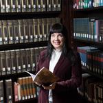 Melanie Masterton Sherazi standing infront of a large bookshelf