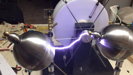 A bright and powerful spark arcs between two metal orbs.