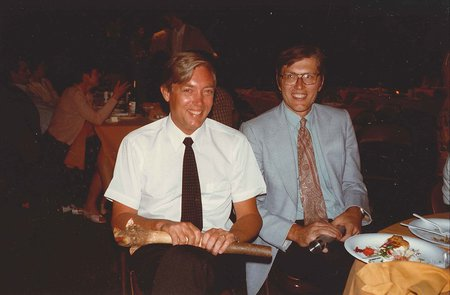 Two men sit at a table in a darkened room and smile at the camera. Other tables and partygoers can be seen sitting at tables in the background.