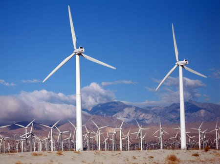 Wind turbines spin in front of a backdrop of clouds and mountains.