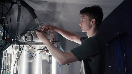 Caltech graduate student Andrew Mueller adjusting the cryogenic equipment where the CQNET quantum detectors are housed