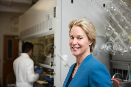 A portrait of Frances Arnold in her laboratory. She wears a blue blazer and smiles at the camera. In the background are laboratory glassware and a researcher at work.