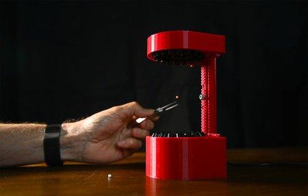 A hand places a pellet into a 3D-printed ultrasonic levitator.