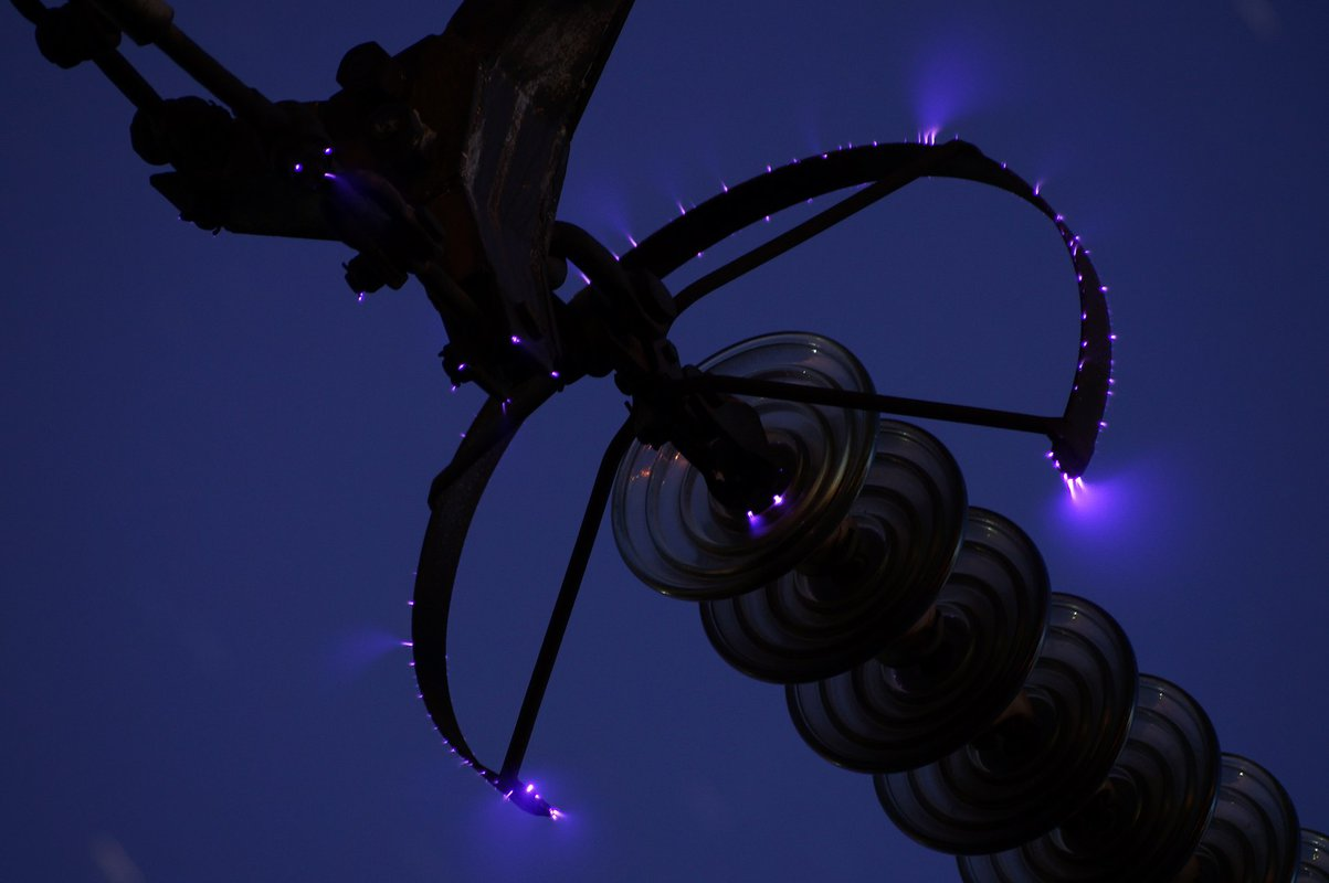 A night-time photograph of a high-voltage power line. Softly feathered electricity leaks off the line's surfaces into the air.
