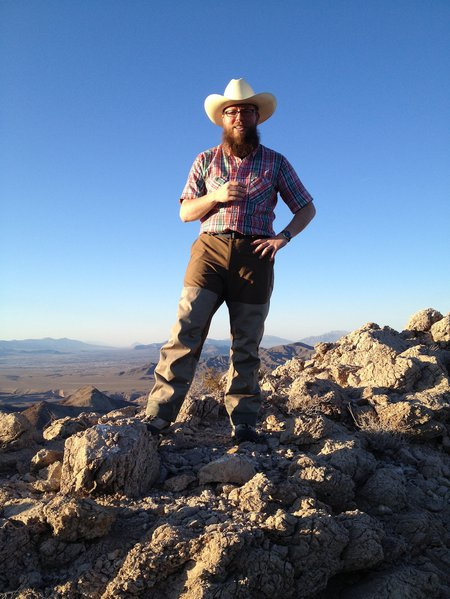 A man wearing a hat and plaid shirt stands among rocks in a dry landscape. Mountains are in the distance