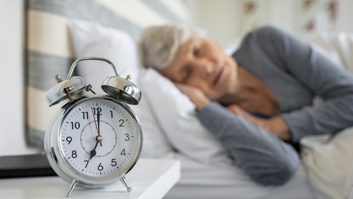 Stock image of a person sleeping next to an alarm clock