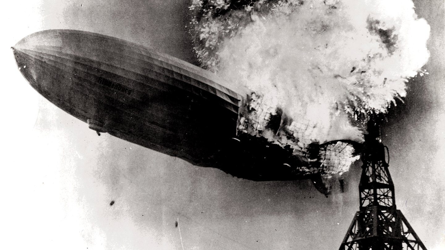 A large zeppelin, partially consumed by flames, begins sinking toward the ground next to its mooring mast. The image is a black and white photograph.