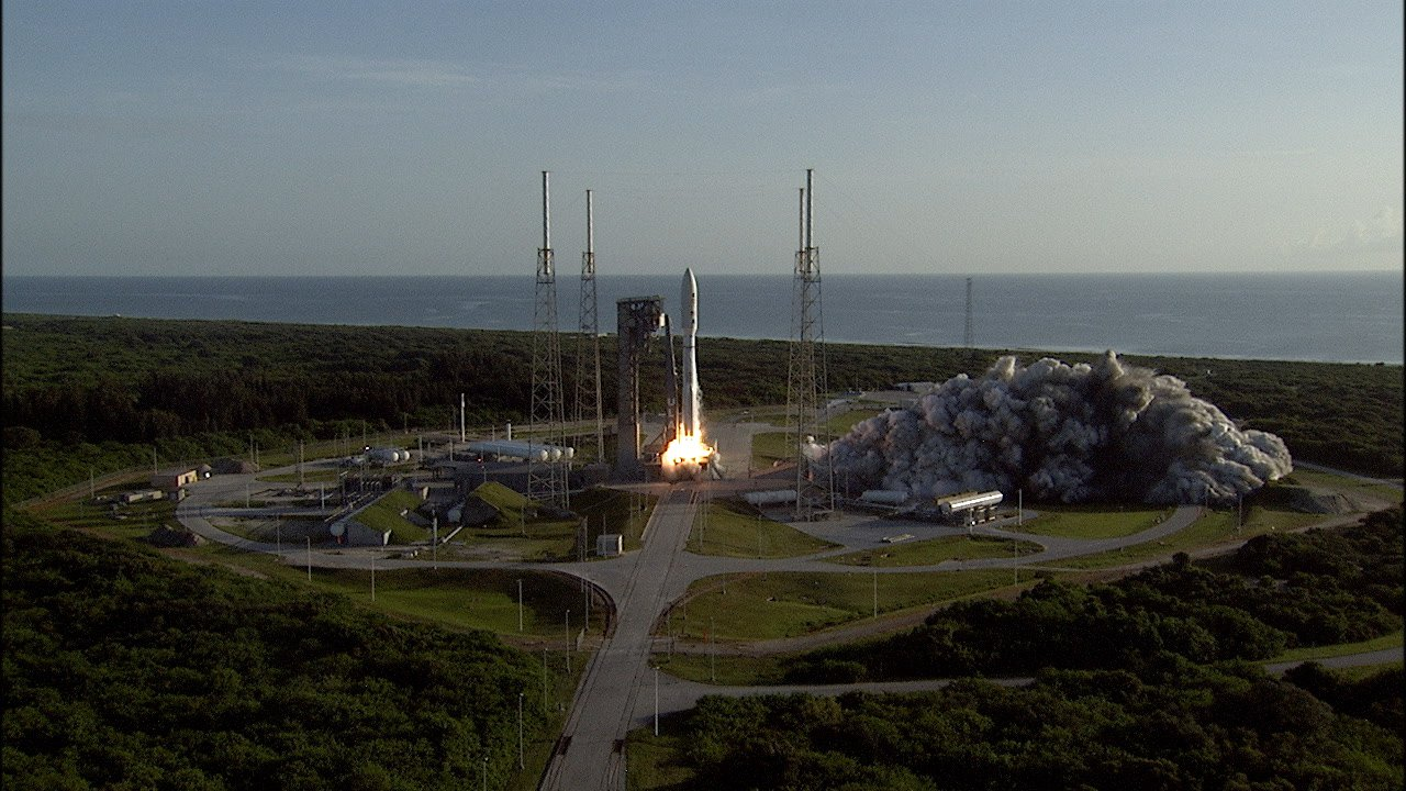A rocket begins launching from its pad, sending smoke and flames outward. Ocean appears in the background.