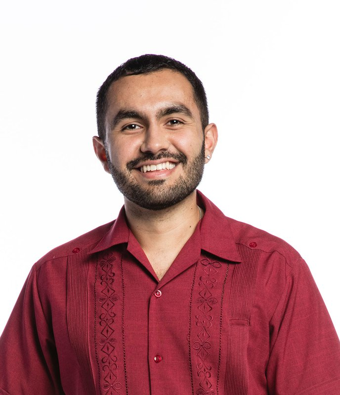 A man in a red button up shirt smiles for a photo