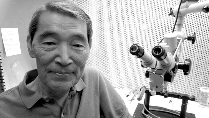 Masakazu (Mark) Konishi next to a microscope