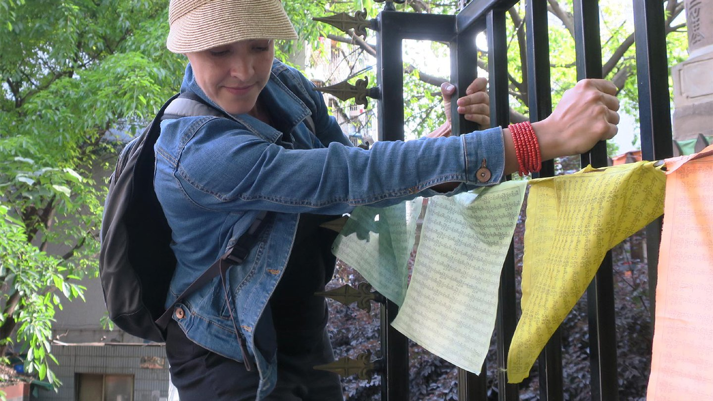 Woman in straw visor climbing a fence with prayer flags attached