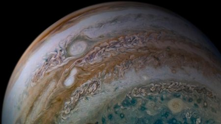 Two white oval storms merge in an orange band on Jupiter