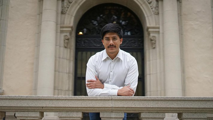 A man with dark hair, glasses, mustache, and white shirt.