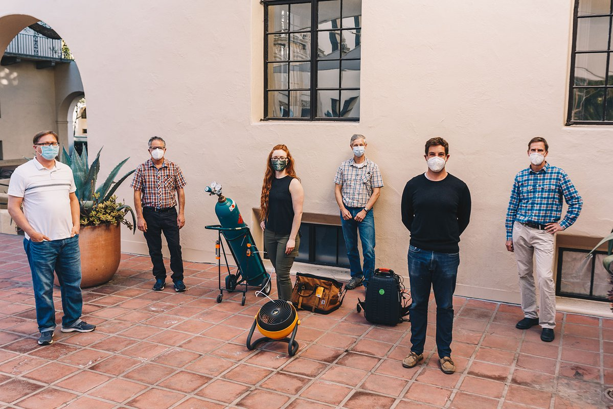 Six people stand outside in masks, posing for a photo next to a large tank of methane and a fan.