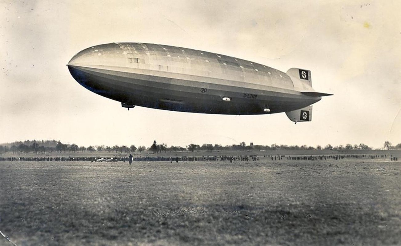 A sepia-toned black-and-white photograph of the Hindenburg hovering over a field. Spectators gathered below are dwarfed by its size.