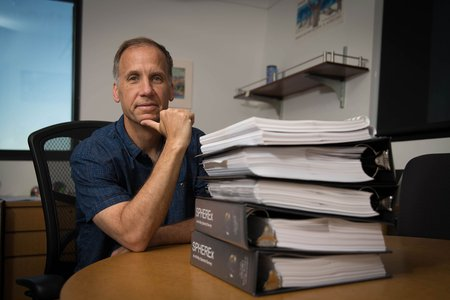 Jamie Bock and a stack of SPHEREx mission proposals.