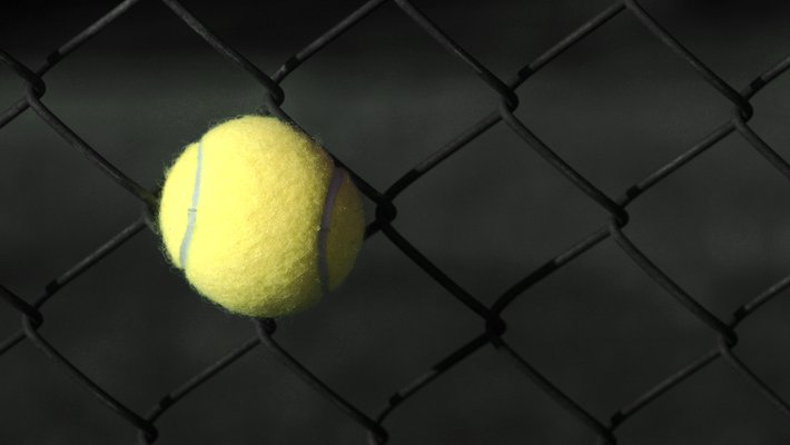 A tennis ball stuck in a chain-link fence.