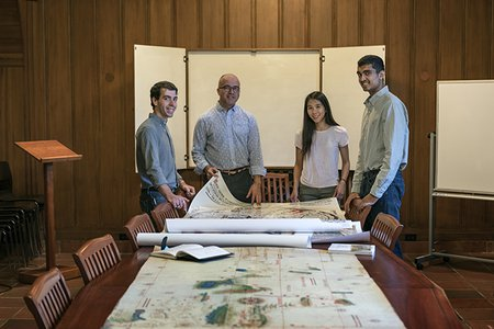 History professor Nicolás Wey-Gómez poses with three students. A series of maps are unfurled on a long table before them