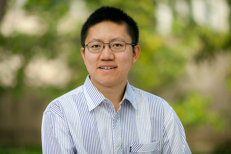 Portrait of Yimeng Li in a striped shirt with green out-of-focus background